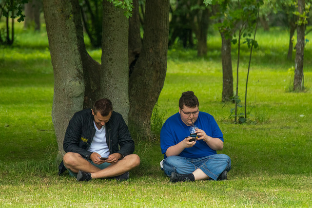two men playing Pokemon Go in the park