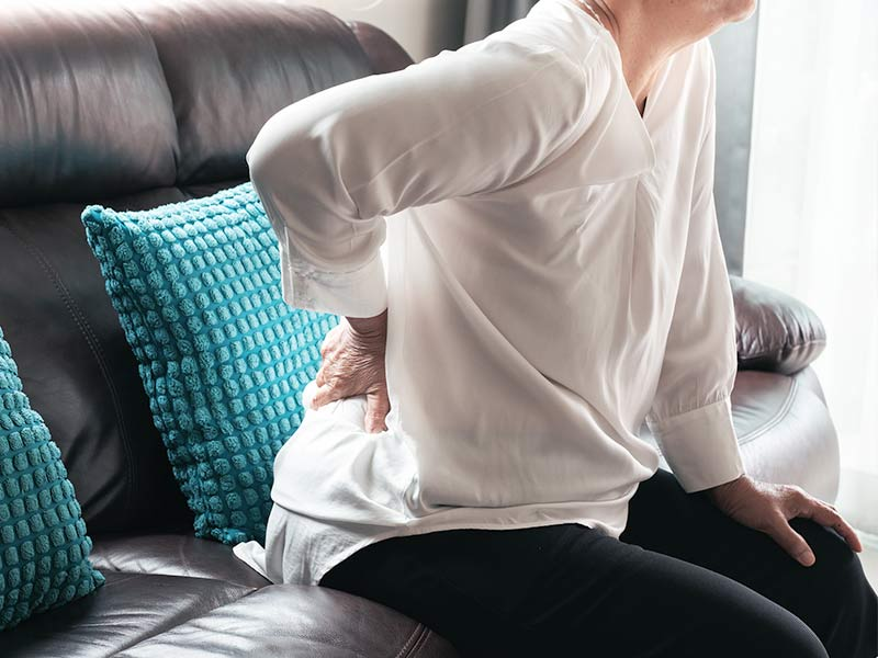 woman pressing on her lower back with her hand