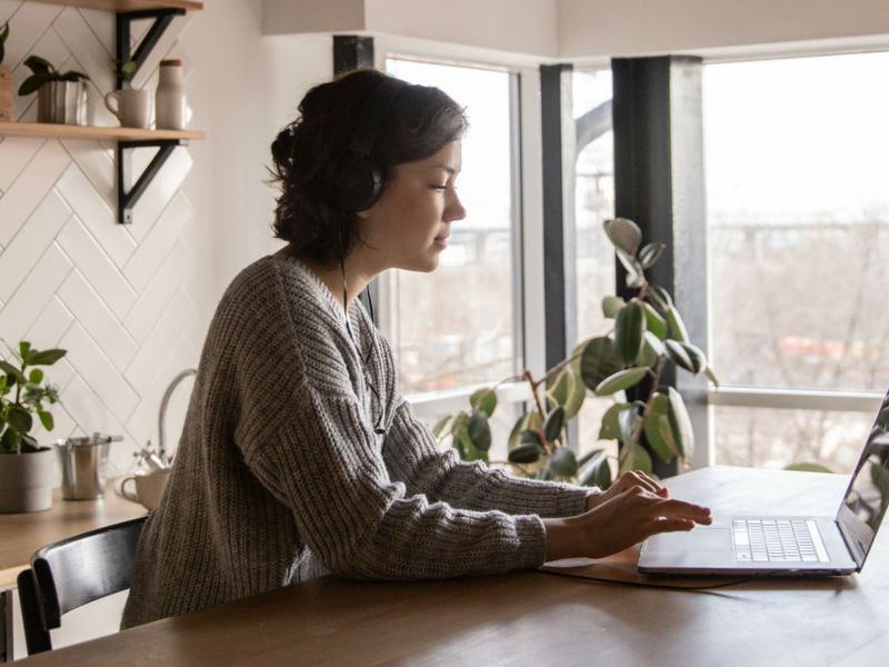 woman working from home sitting at kitchen table