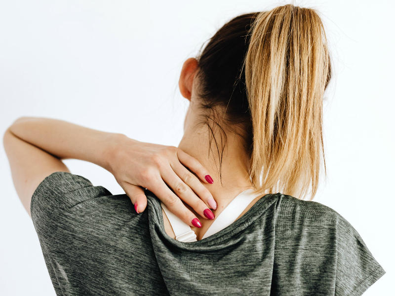woman reaching for lower back neck