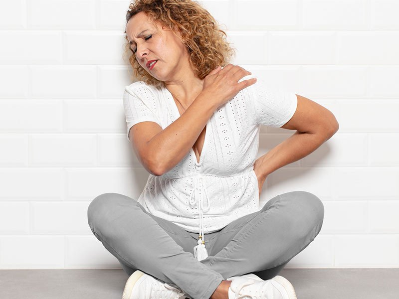 woman try to soothe her own back pain
